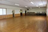 Intérieur de la salle des loisirs de La Plaine-sur-Mer avec chaises et tables
